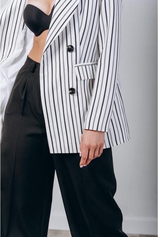 Классический костюм двойка. Белый с черным паттерном в узкую полоску пиджак. Черные брюки.