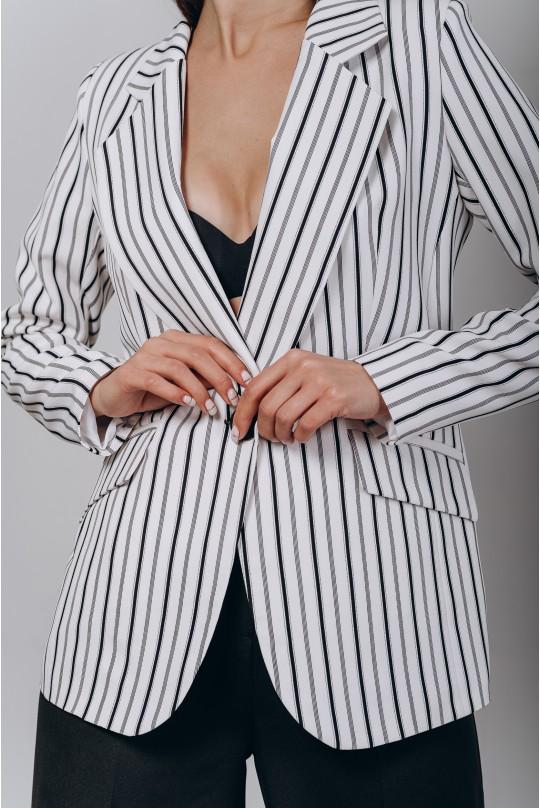Классический костюм двойка но одну пуговицу. Белый с черным паттерном в узкую полоску пиджак. Черные брюки.